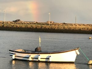 Anchored boat and rainbow